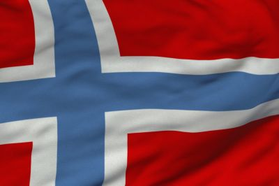 The flag of Norway is red with an indigo blue Scandinavian cross outlined in white that extends to the edges of the flag